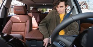 A young driver buckles his seatbelt in a Chevrolet Traverse