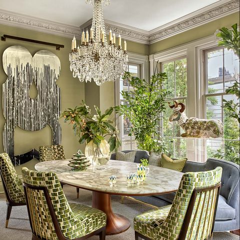 Green chairs around marble table with blue banquette