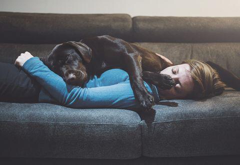 chica durmiendo en el sofá junto a su perro