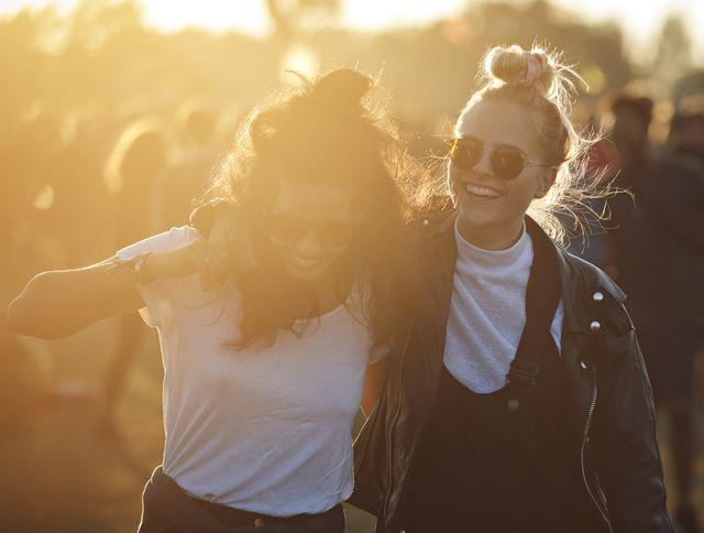 dos chicas jóvenes riéndose en un concierto de música