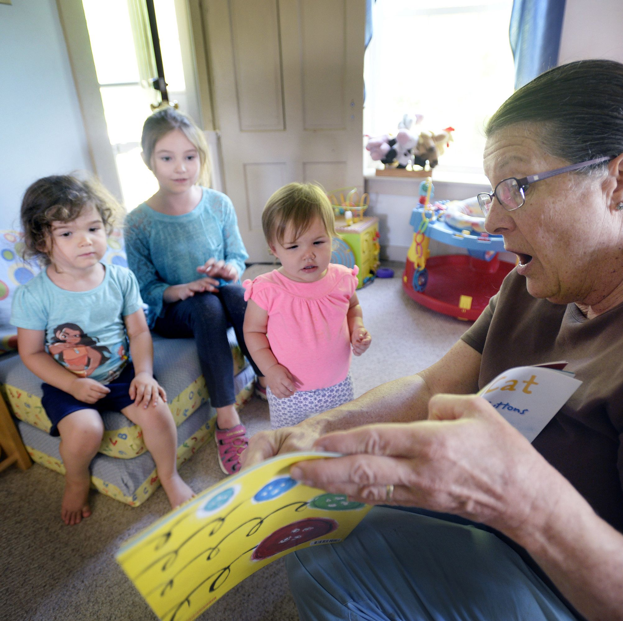 A child care worker in Maine reads to three charges.