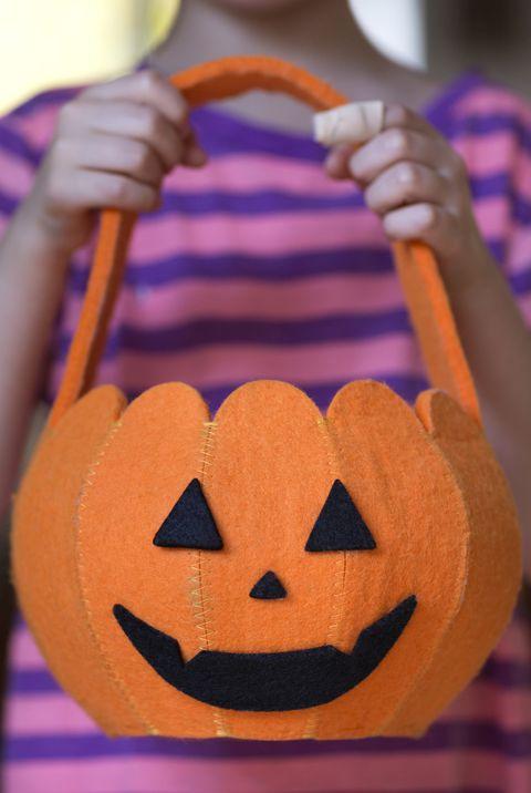 child 6 7 holding pumpkin shaped halloween bag