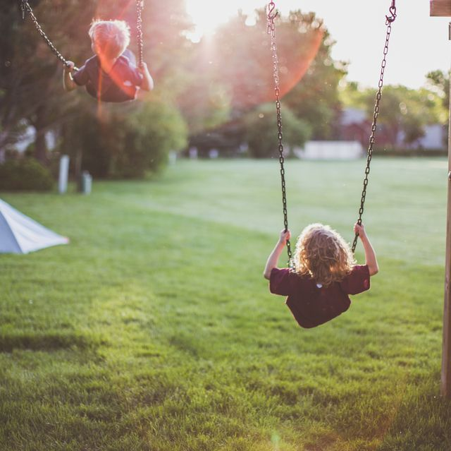 back view of a little boy and little girl swinging high into the sky as the sun sets behind them while a tent is set up in the yard