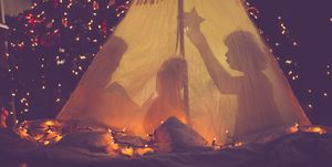 Children in tent in front of Christmas tree