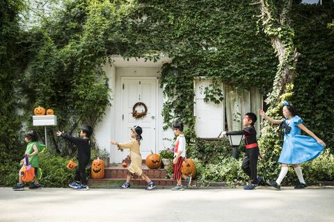 Children marching in front of the house wearing costumes.