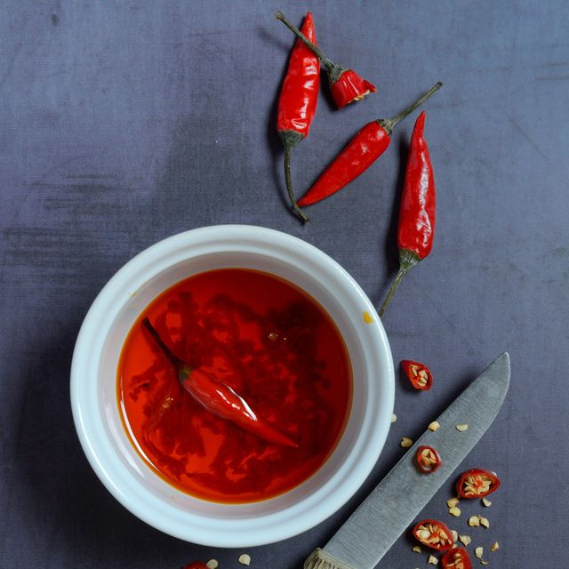 chili oil in bowl with knife and chili peppers, food photography, studio shot, germany