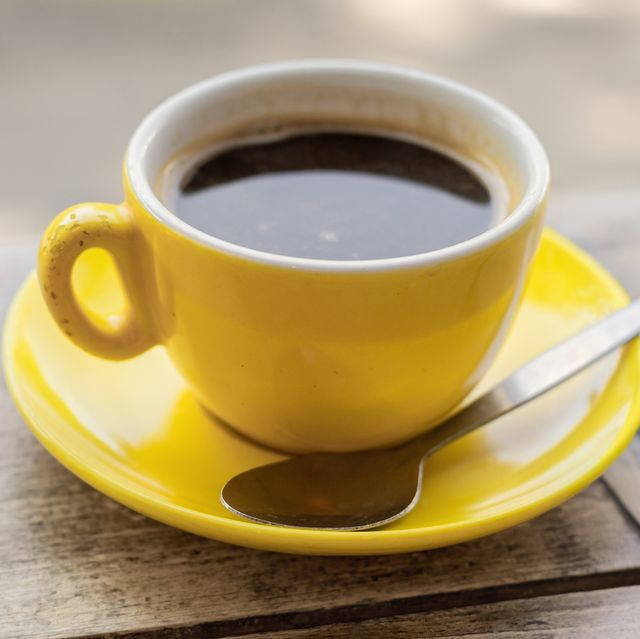 Chipped yellow coffee cup and saucer on a wooden table,