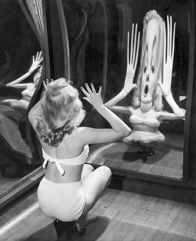 nothing that alice ever found behind the looking glass could be half as weird as the reflection produced by blonde canda loden as she tests one of the new trick mirrors at the rockaways playland  location queens amusement park, borough of queens, new york, usa