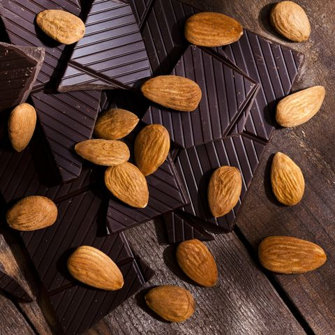 Chocolate pieces and almonds on rustic wood table with copy space