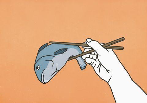 chopsticks holding whole dead fish