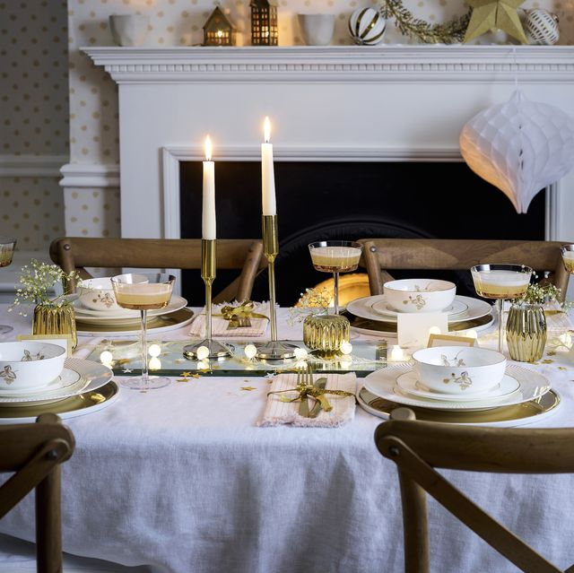set an elegant table with smart china, a few retro chic pieces and a classic, understated backdrop add white and gold china to a white linen tablecloth and introduce a mirrored charger as a centrepiece that reflects the glow from a string of fairylights brushed gold cutlery, 1970s style candlesticks and champagne coupes complete the looklower george st wallpaper in quartz, £57 a roll, little greene carisbrooke extending dining table, £439, barker  stonehouse camargue weathered oak dining chairs, £189 each, oka linen tablecloth, £135, the linen works simone cups, £17 each gold fluted votives, £33 for three all bloomingville walther  co brass houses, from £2550, the scandinavian shop baubles, £2150 each tall star shaped tealight holder, £2995 canvas home dauville gold plates, £36 each all selfridges gold wreath, £25 bauble light chain, £1999 brushed gold cutlery, £16 for four all rockett st george party porcelain gold hanging star on mantelpiece, £12 for three honeycomb decoration, £11 for three party porcelain gold star scatter, £350 a pack gold ribbon, £750 a pack all talking tables glass cakestand below, £20, nordic house crackers on cakestand, £20 for 12 caspari gold moire placecards, £350 for 10 jasper conran for wedgwood gold dinner plates, £35 each gold band side plates, £10 each wedgwood wild strawberry bowls, £20 each all john lewis rectangular mirrored charger, £35, the white company lsa edge champagne saucers, £42 for two, houseology upper half candlesticks, £6325 for two, broste copenhagen shimmer stripe napkins, £28 for four, anthropologie