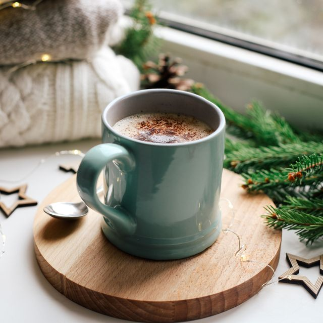 cozy home picture of blue ceramic cup with coffee on window sill, christmas decorations, warm knitted sweaters and pine tree green branches in background