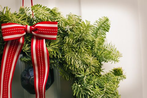 Christmas decorations. A Christmas wreath with a red bow on the front door of a house.