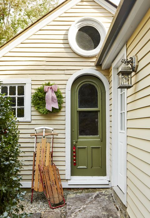 green front door with christmas bells hanging from the door knob and sleds leaned up against the house