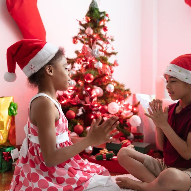 two kids wearing santa hats playing a game in front of the tree