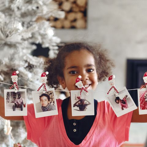 christmas celebration with family and friends little girl holding polaroid pictures