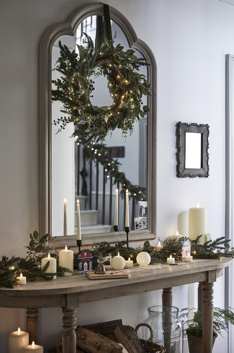 christmas hallway decorations with wreath above the mirror and candles on console table