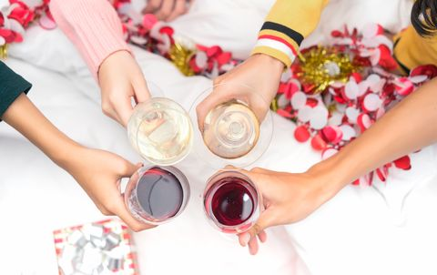 Christmas home party cocktail clink concept, Closeup hands holding glass of wine, champagne friend drinking celebration interior, Top view.
