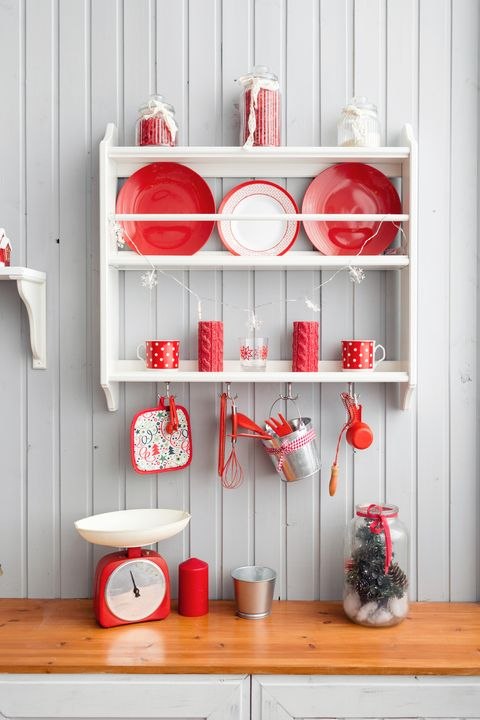 shelves with dishes. Interior light grey kitchen and red christmas decor. Preparing lunch at home on the kitchen concept.
