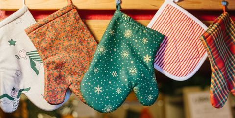 Christmas mittens potholders hang in kitchen against the background of blurry kitchen appliances.