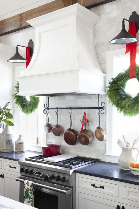 a marble backsplash and white hood range cover with copper pots hanging on a rack underneath and a holiday wreath on each side