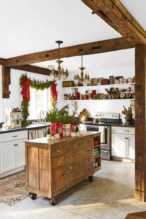 an all white kitchen with reclaimed wood beams and an antique kitchen island on wheels is set for the holidays with vintage tins and santa mugs holding bottle brush trees