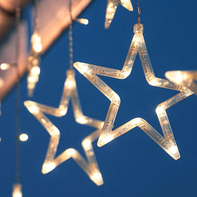 star christmas lights hanging against blue sky
