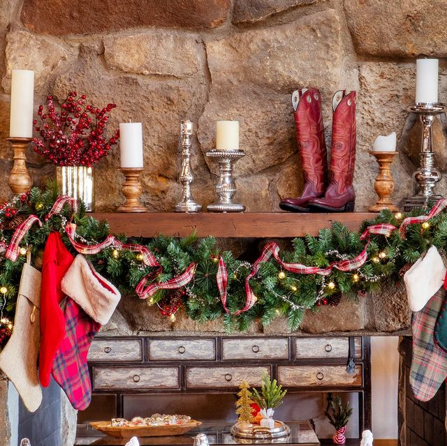 christmas mantel decorated with garland, ribbon, candles, and cowboy boots