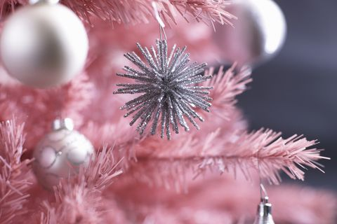 Christmas ornaments on pink Christmas tree, close-up