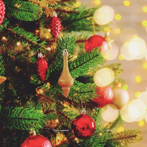 Christmas spirit concept. Pine tre with decorations on festive bokeh background.