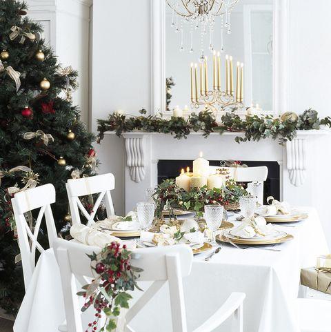 Salle à manger blanche décorée pour Noël, décor de table avec vaisselle en or et blanc, bougies allumées, verres à vin, table basse décorée de baies et baies, miroir de cheminée avec nappe au dos, lanterne dorée, sapin de Noël avec ruban