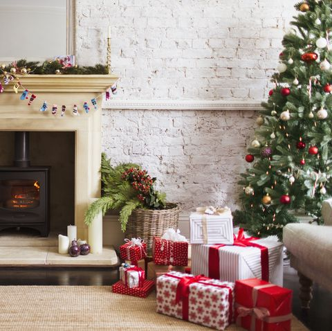 Christmas tree, gifts and decorations near fireplace in living room