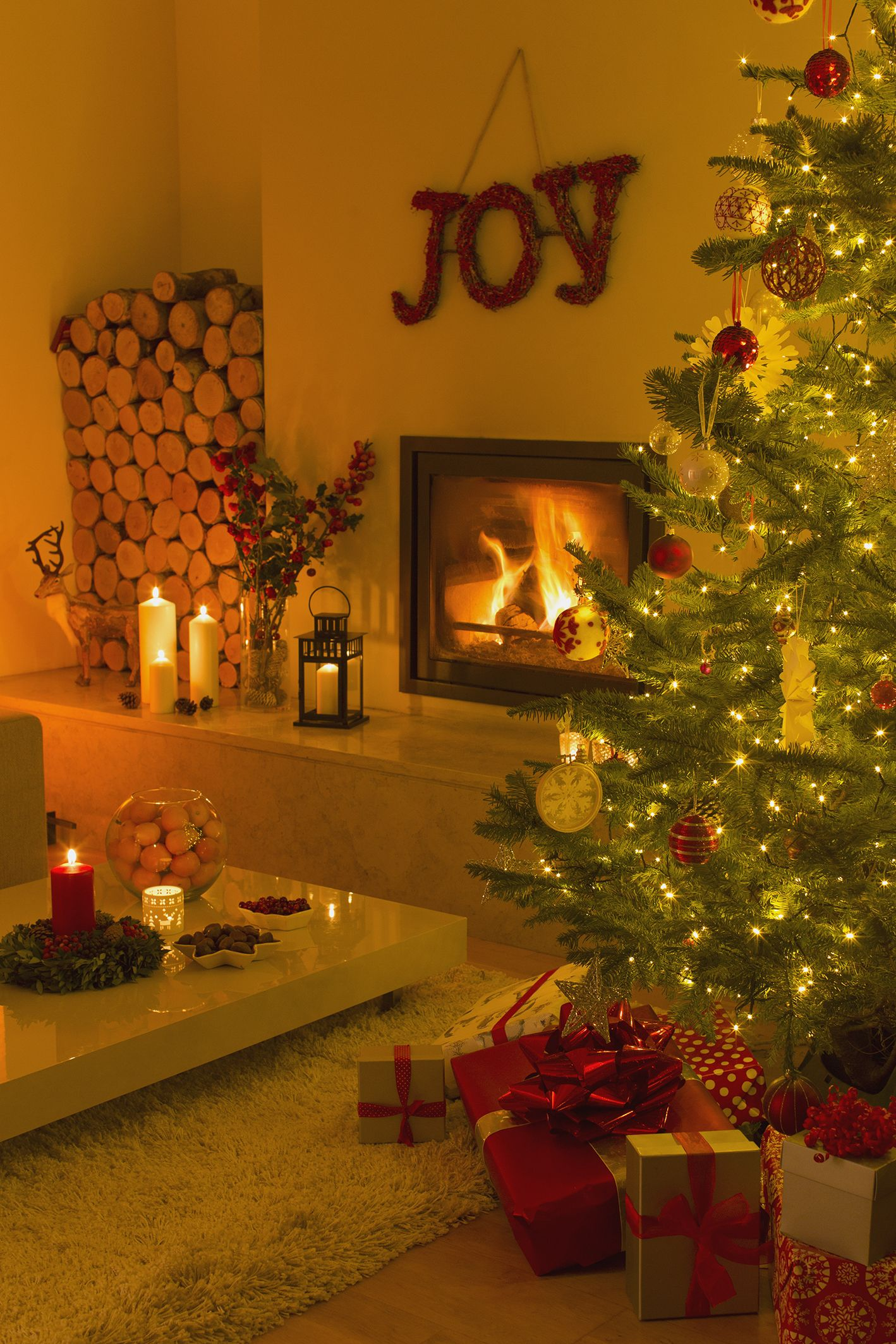 Ambient Fireplace And Candles Illuminating Living Room With Christmas Tree  And Decorations