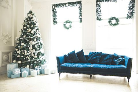 christmas living room with a christmas tree sofa gifts and a large window