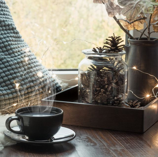 still life in home interior cozy winter or autumn cup of coffee at home warm fluffy furskin , garland, swedish hygge concept