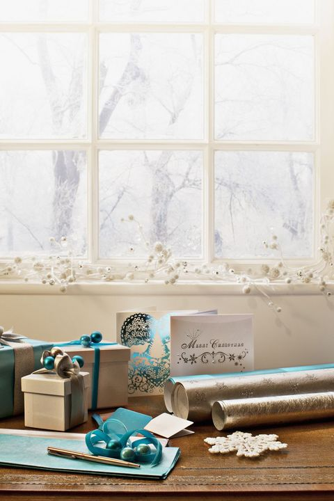 Christmas wrapping paper, ribbon, ornament and cards near window