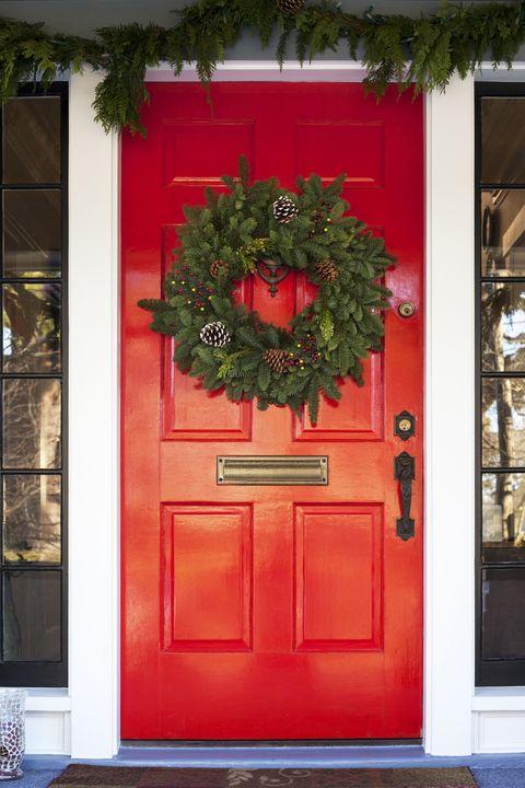 Christmas wreath hanging on red door