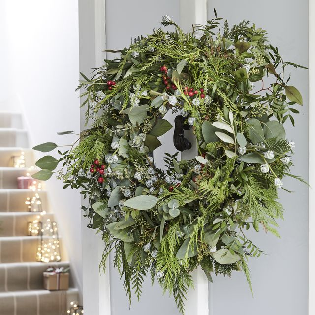 christmas decoration   a real handmade green wreath on the front of an open white door, staircase in the background