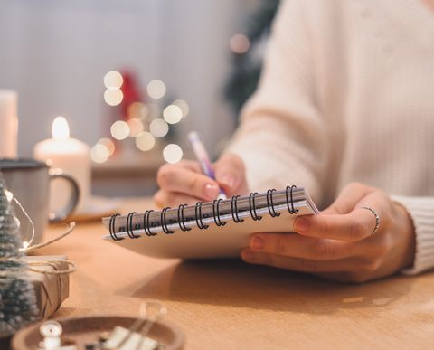 goals plans make to do and wish list for new year christmas concept writing in notebook woman hand holding pen on notepad at home on winter holidays xmas
