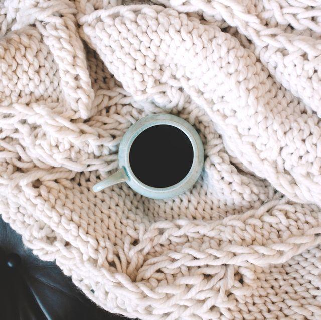 coffee mug on top of chunky knit throw blanket