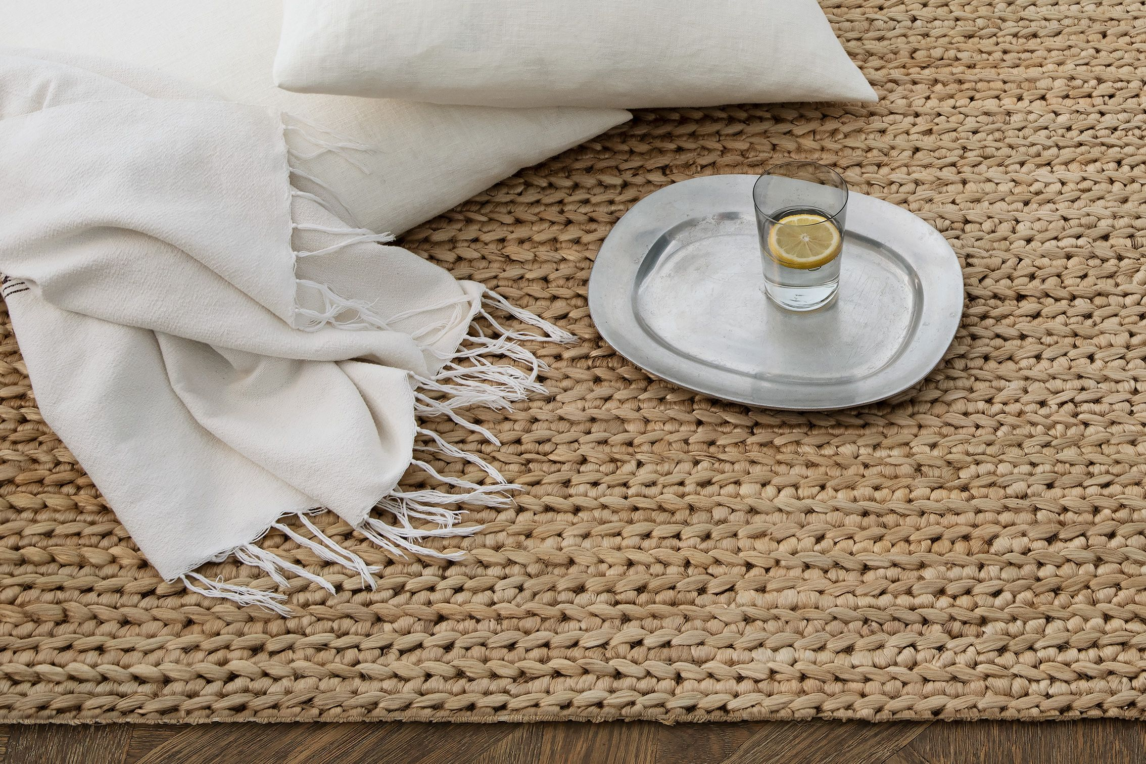 Chunky hand-braided jute rug in linen, from $445.