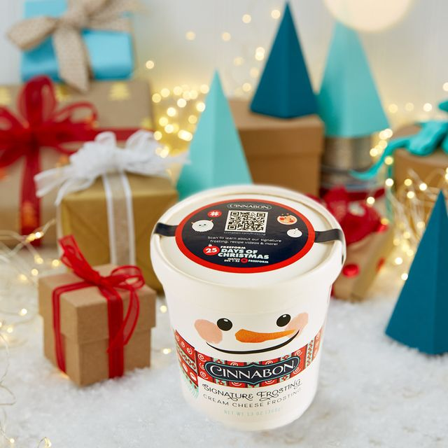 cinnabon signature cream cheese frosting in a snowman themed pint container surrounded by brown gifts with white and red bows