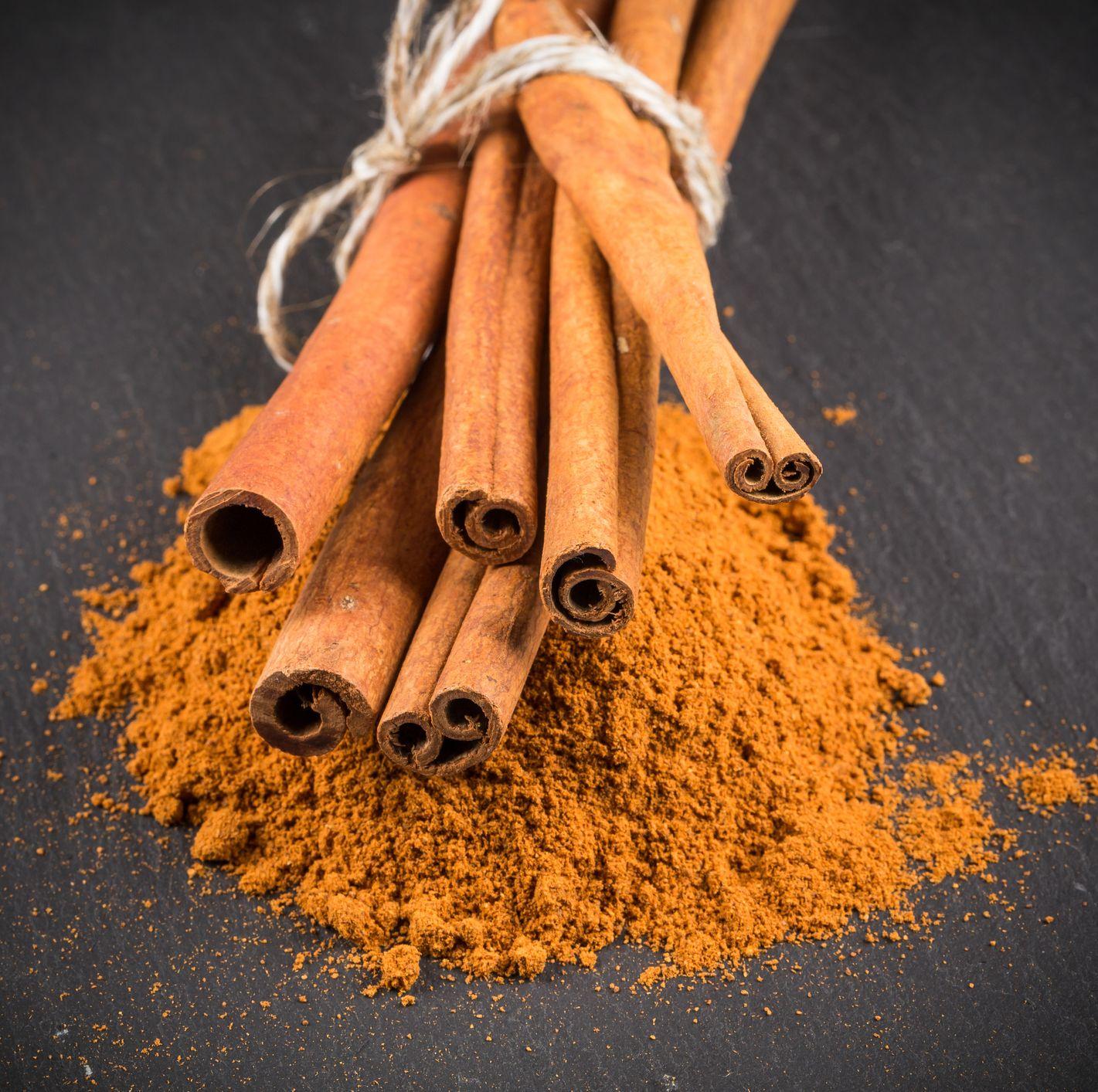 cinnamon sticks with powder on dark stone background