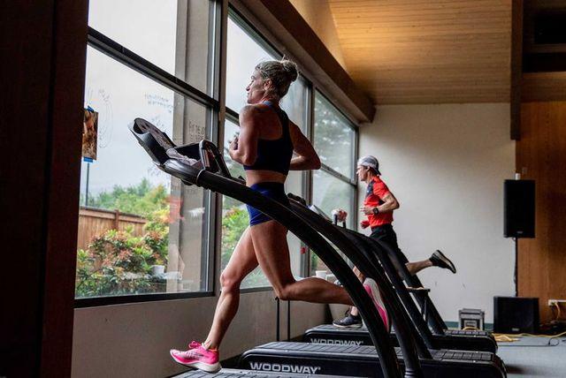 una mujer y un hombre corren en la cinta de correr de un gimnasio