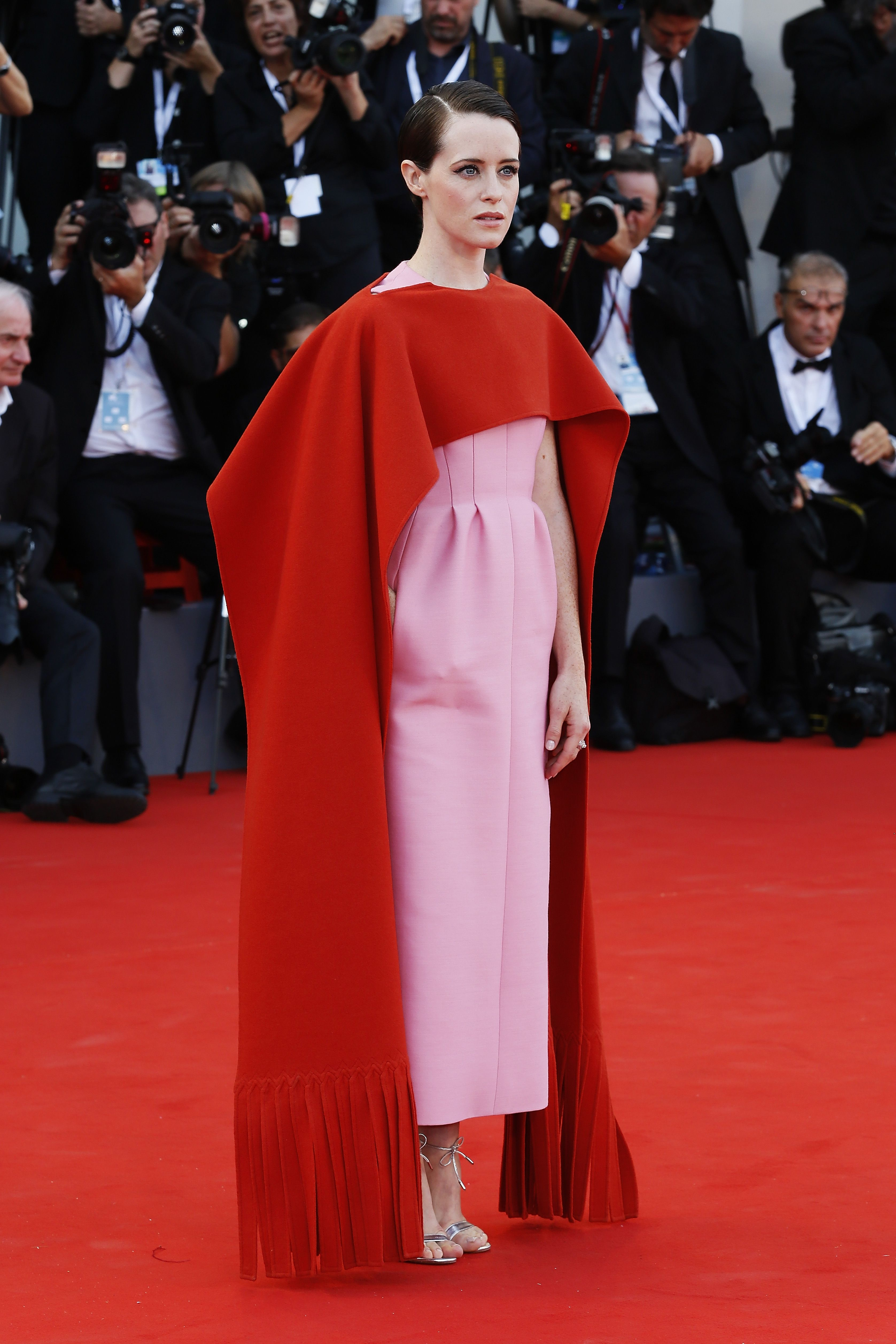 The Crown star stunned on the red carpet at the Venice Film Festival in a structured pink Valentino gown with a red fringe cape.