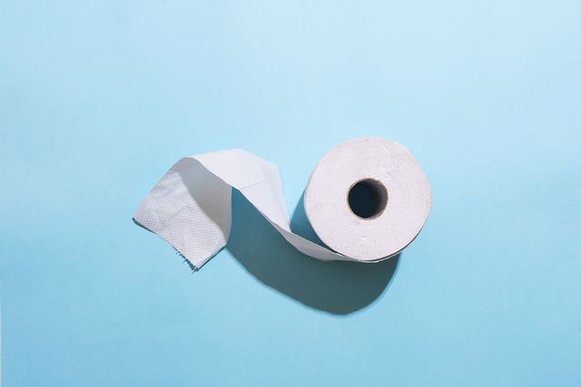 roll of toilet paper against light blue background