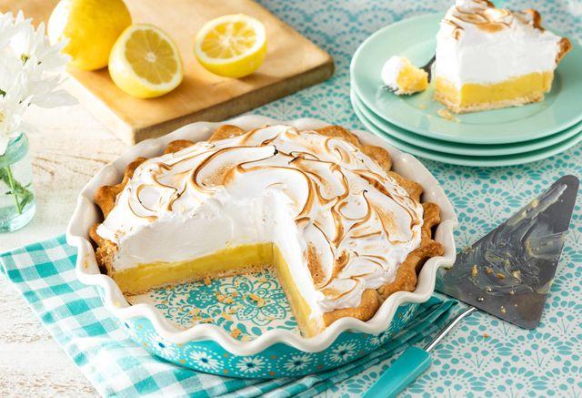 classic lemon meringue pie with slice cut out and lemon slices