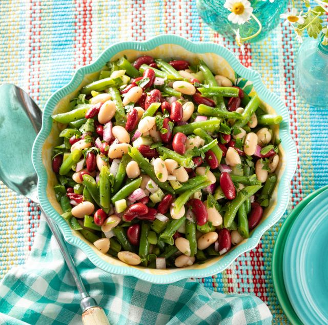 classic three bean salad in blue bowl with big spoon and flowers