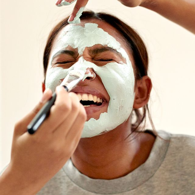 three women applying clay masks to face