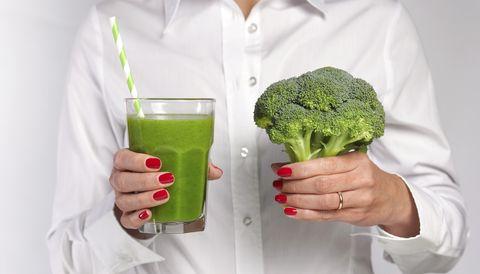 一個女生一手拿綠色果汁一手拿花椰菜